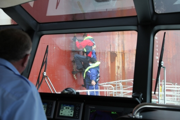 Clambering from the pitching deck of a launch on to a swaying, slippery rope ladder dangling over the ship's side is a hazardous job for sea pilots.